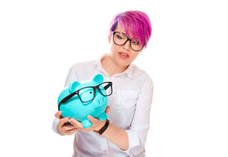 Scared shocked woman worried over savings on buying eyeglasses. Piggy bank and girl wearing glasses isolated on white background. Negative facial expressions human face emotions body language reaction 免版税图像