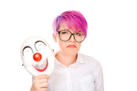 Portrait young upset worried woman with sad expression taking off clown mask expressing cheerfulness happiness isolated on white wall background. Negative facial expressions, human face emotions.
