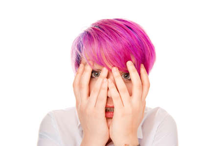 Scared young woman covering her face with hands peeking through fingers isolated on white background. Studio shot horizontal image. Negative face expression, human emotions feeling attitude, reaction.