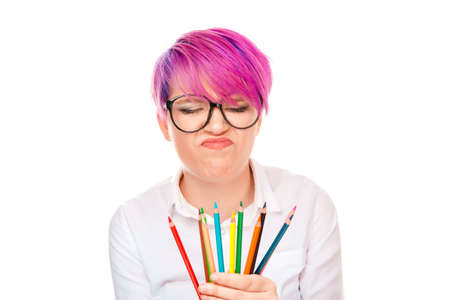 Young grumpy woman with pink hairstyle wearing eyeglasses and shirt holding set of colorful pencils looking down frowning in disappointment isolated on white background Negative facial face expression