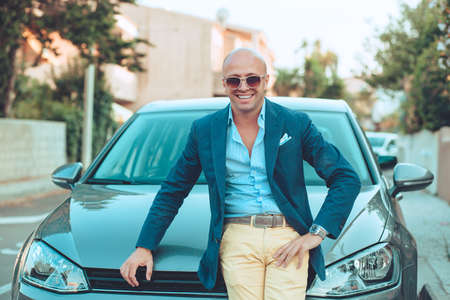 Cheerful italian young man standing near his car in front of his house laughing smiling happy, sunglasses on eyes posing next to his car outdoors urban road background. Positive face expression 免版税图像
