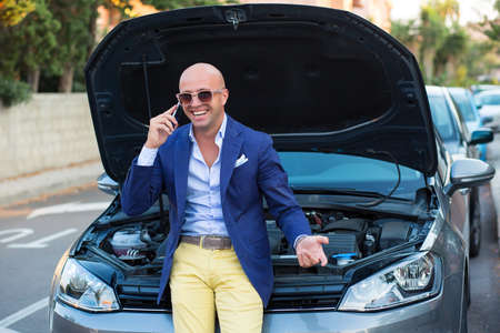 Portrait of confident male business man sited on his car with open hood happy with it laughing and talking by phone happily outdoors urban road background. Positive face expression human emotion