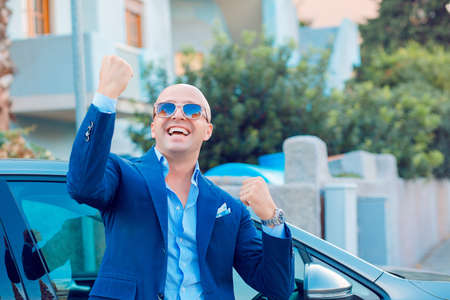 Yes! That is my new car, customer in the parking lot young man fist in air celebrating with key in hand standing next to his car outdoors urban background. Positive face expression emotion reaction 免版税图像