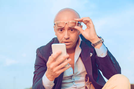 Anxious upset young shocked man looking at phone seeing bad news or text message sitting outside blue sky on background. Negative face expression human emotion reaction body language attitude