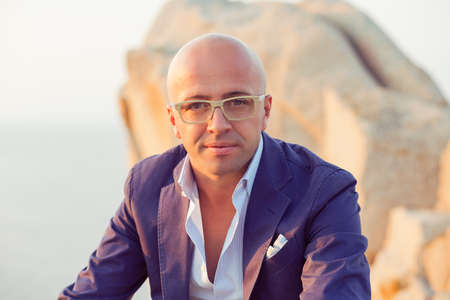 Portrait of a confident pensive Caucasian bald man in eyeglasses looking at you camera sitting outdoors big rocks on background. Positive face expression human emotion reaction body language attitude