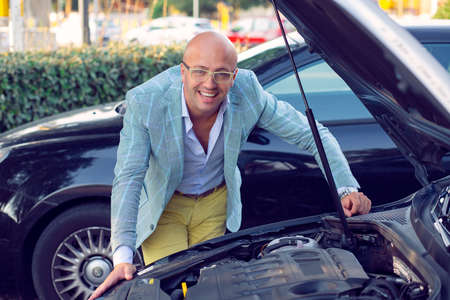 Business man, seller in the the dealership showing the car engine carburetor concept smiling happy outdoors urban  background. Positive face expression human emotion reaction body language