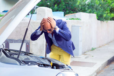 Stressed man having trouble with his broken car looking in frustration at failed engine; hands on head looking inside to the open capote top of the car. Negativehuman emotion reaction body language 免版税图像