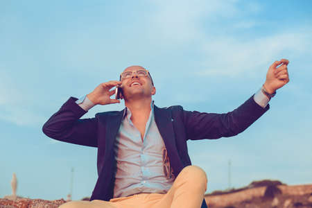 Businessman getting phenomenal news on the phone sitting on rocks fists hands in the air celebrating outdoors blue sky on background. Positive face expression emotion reaction body language attitude