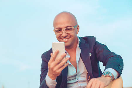Happy bald business man smiling man looking at mobile phone sitting on rocks outdoors blue sky on background. Positive face expression human emotion reaction body language attitude 免版税图像