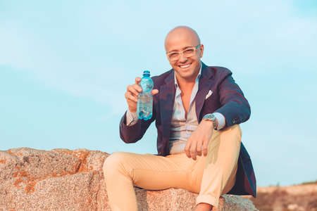 Hydrate yourself. Closeup portrait thirsty middle mature man giving you bottled water outside isolated sitting on rocks utdoors blue sky on background. Positive face expression emotion body language