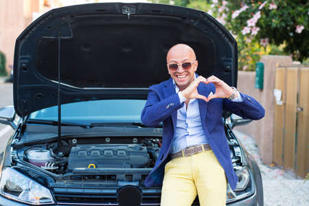 I love my engine car. Handsome man showing heart hand gesture standing near his new car with open hood standing next to his car outdoors urban road background. Positive face expression human emotion