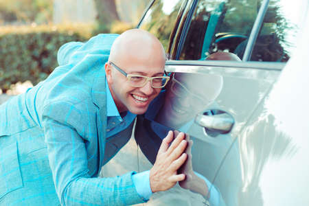 Happy excited young bald italian man driver embracing petting his car outdoors. Green energy biofuel electric environment friendly new car concept.  Positive face expression human emotion reaction
