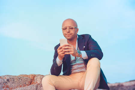 Closeup portrait puzzled confused business man looking at smartphone thinking reply to received sitting on rocks blue sky on background. Negative face expression human emotion reaction body language Stok Fotoğraf