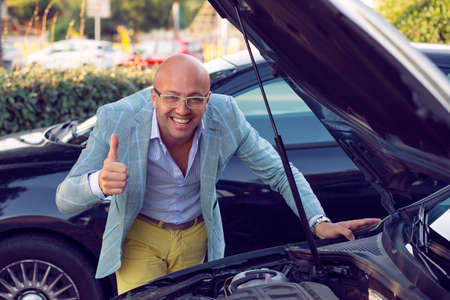 Happy smiling man showing thumbs up standing next to his car with open hood showing engine inside capote, handsome guy excited about his new vehicle outdoors background. Positive face expression