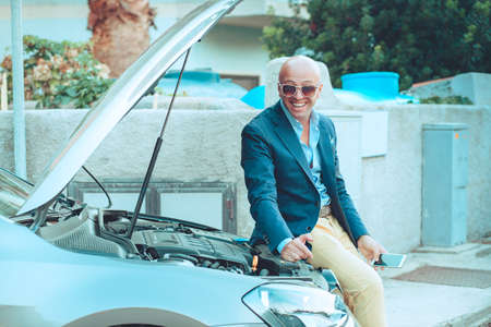 Business man, happy driver sitting on his car with opened hood showing the car engine carburetor smiling looking at you camera isolated outdoors urban  background. Positive face expression emotion
