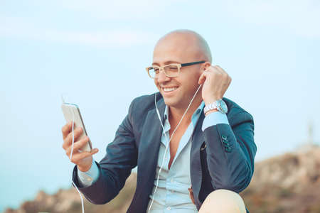 Handsome smiling businessman guy having fun listening to music on phone spending time outdoors sitting on rocks blue sky on background. Positive face expression human emotion reaction body language
