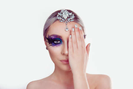 Beautiful woman beauty with artistic purple blue eyes makeup feather on eyelashes holding silver jewelry on head showing manicure nail polish isolated white background. Blue black bird swan makeup art concept