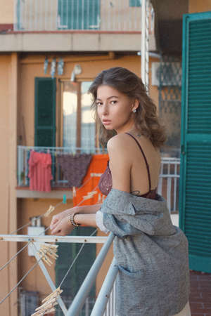 Fashion style portrait of a beautiful woman in casual gray jacket clothing on an Italian balcony looking back at camera. Stok Fotoğraf