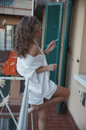 Fashion style portrait of a beautiful woman smoking a cigarette and posing in white shirt on an Italian balcony and looking ahead throug the window posing