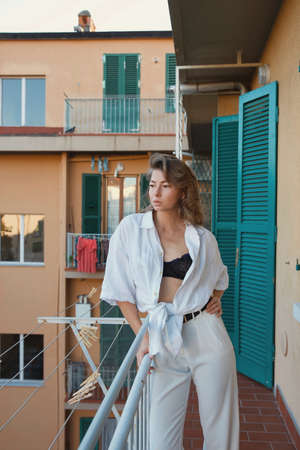Fashion style portrait of a beautiful woman in casual white shirt clothing on an Italian balcony looking at camera.