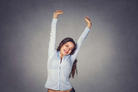 Happy smiling young woman stretching her arms wearing formal blue shirt stretching isolated on gray background.