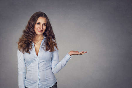 Closeup portrait happy confident young smiling woman gesturing, presenting copy space at right with open palm up isolated grey wall background. Positive human emotion sign symbol face expression