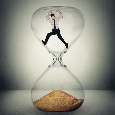 Time is ticking concept. Everything is temporary, nothing is eternal conceptual photo manipulation. Closeup of hourglass with man inside about to be wasted, to die, to be transformed in sand isolated on gray background.
