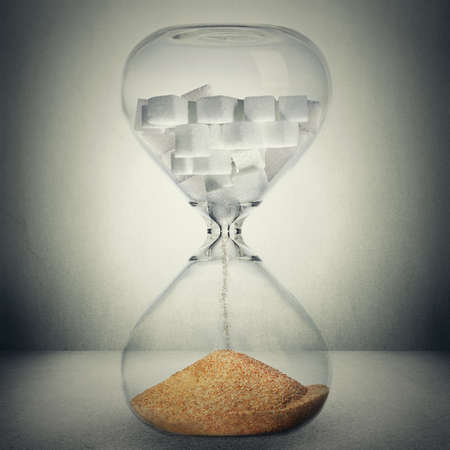 Sugar kills in time, death concept. Closeup of hourglass with sugar in cubes that is pouring down transforms in sand or gold, meaning making sugar is very profitable business isolated on gray background