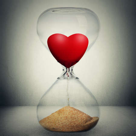 Even love is not eternal concept. Love is temporary conceptual photo manipulation. Closeup of hourglass with heart inside pouring down transforming into sand isolated on gray background.