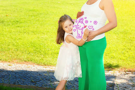 Cute little girl hugging and kissing her mothers pregnant belly in summer nature outdoors in a city park