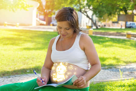 Pregnant woman reading book sitting outdoors on a green grass meadow in a city park on a sunny day. Sun flare on background, glowing drawing on her belly