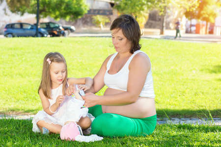 Kid girl withpregnant mom resting playing with a doll in park on green grass. Girls playing with toys. Both and wearing white clothing dresses. Picnic outdoors on warm summer day. Copy space Stok Fotoğraf