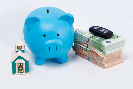 Stack pile of european money, Euro cash currency with a car key on it, a piggy bank next to it and a home on it isolated on white background. Savings for a new home and car, real estate property mortgage leasing concept.