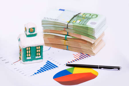 Stack pile of european money, Euro cash currency on a graphic chart and a home on it isolated on white background. Savings for a new home, real estate property mortgage business conceptual image.