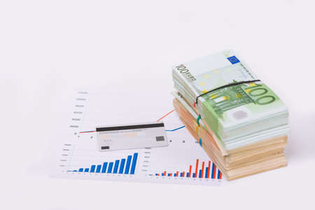 Stack pile of european money, Euro cash currency on a graphic chart and a pen on it isolated on white background. Savings for a investing in stock market, credit for business conceptual image. Stok Fotoğraf