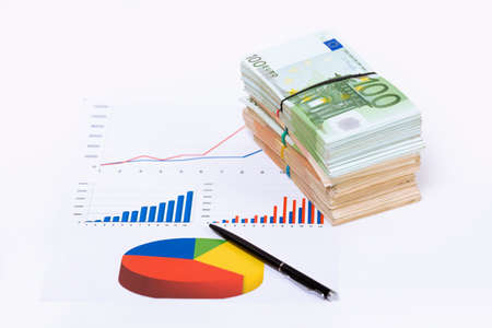 Stack pile of european money, Euro cash currency on a graphic chart and a pen on it isolated on white background. Savings for a investing in stock market business conceptual image. Stok Fotoğraf