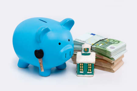 Stack pile of european money, Euro cash currency, a piggy bank with a key on it and a home on it isolated on white background. Savings for a new home, real estate property mortgage concept. Stok Fotoğraf