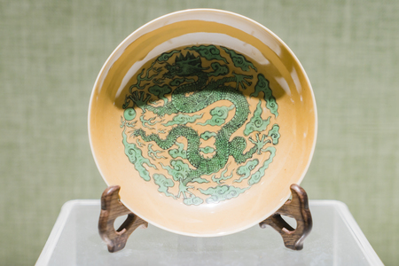 Qing Dynasty yellow earth green dragon porcelain plate at at museums, Shandong Province, Qingdao, China. Redakční