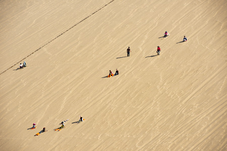 Gansu, Dunhuang, Mingsha Mountain Crescent Spring Scenic Area, tourists on the sand hill