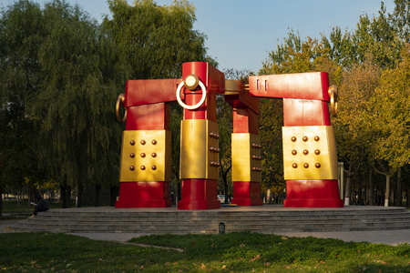 A student is reading a book at Hebei University of Economics and Business outdoor sculpture, Shijiazhuang, Hebei, China