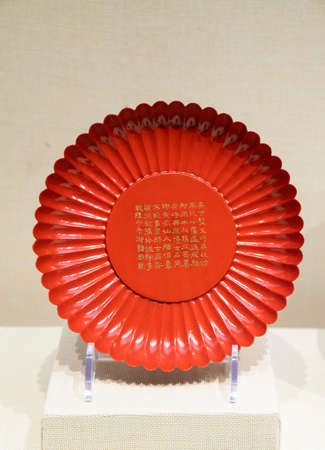 Qianlong red lacquer chrysanthemum petal plate from Qing Dynasty at Kaifeng Museum, Kaifeng City, Henan Province, China.