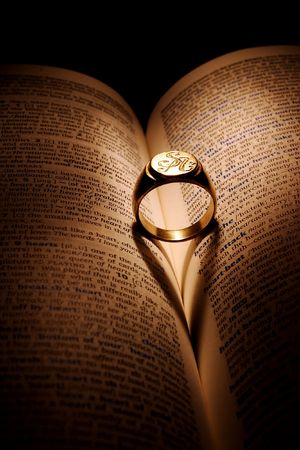 Golden ring on a book, Light that is falling on the ring is creating image of heart