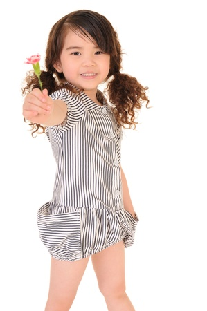 Happy little girl holding a carnation. Isolated on white background
