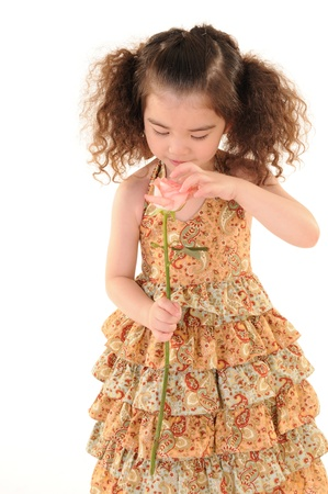 The little girl holding a flower  Isolated on white background Stock Photo - 13509740