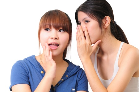 Two young casual woman gossiping isolated against white background
