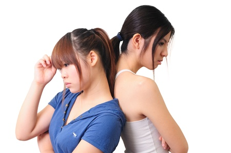 studio shot portrait on isolated background of two sisters women friends thinking looking up photo