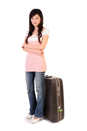 A beautiful brunette waiting to travel with a suitcase  Isolated on a white background