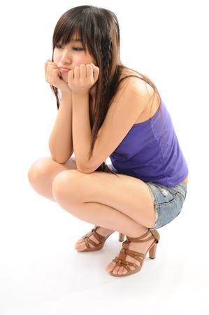 en cuclillas: Chica linda en cuclillas sobre el fondo blanco