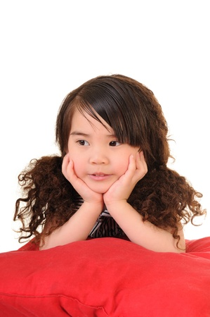 The little girl lying on red pillow  Stock Photo