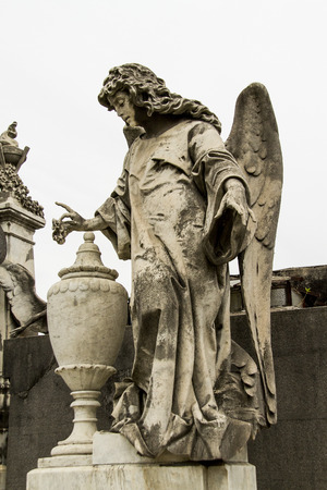 mortality: angel statue in the cemetery guarding the graves of the dead.